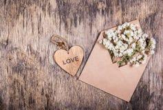 Белые цветки в бумажном конверте и деревянном сердце St День ` s Валентайн Предпосылки и шаблоны Стоковое Фото