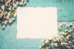 Белые цветки и бумажная карточка на голубой деревянной предпосылке празднично Стоковая Фотография RF