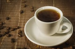 Белые чашка кофе и кофейные зерна на темной деревянной предпосылке/белых горячих чашке кофе и кофейных зернах на темное деревянно стоковое изображение rf