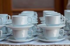Белые чашки для чая сложенного на таблице с плитами для перерыва на чашку кофе Концепция ресторанного обслуживании Стоковая Фотография RF