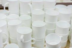 Белые чашки на полке в магазине Белые керамические кофейные чашки и поддонники на полках Полки с утварями кухни стоковые фотографии rf