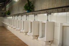 Белые чистые керамические шары писсуара в туалете общественных людей рядок Стоковая Фотография RF