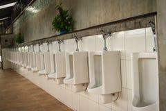 Белые чистые керамические шары писсуара в туалете общественных людей рядок Стоковая Фотография