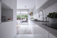 Белые шкафы в ярком современном интерьере кухни дома с террасой Реальное фото стоковые изображения rf