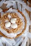 Белые яйца в декоративном гнезде на деревянной плите Настроение пасхи концепции пасхи стоковые изображения