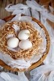 Белые яйца в декоративном гнезде на деревянной плите Настроение пасхи концепции пасхи стоковые фотографии rf