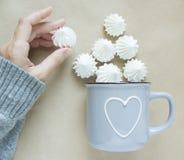 Белые merengues в чашке на бежевом взгляде сверху предпосылки Чашка с сердцем в женщинах вручает стоковая фотография
