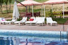 Белые sunbeds бассейном на открытом воздухе Стоковая Фотография RF