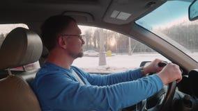 Белый автомобиль водителя водителя на шоссе Уставший но счастливый человек в кивках автомобиля возглавляет к музыке смотря камеру акции видеоматериалы
