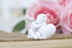 Белый ангел Красивые розовые цветки на белом столе Стоковая Фотография