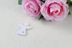 Белый ангел Красивые розовые цветки на белом столе Стоковые Фотографии RF