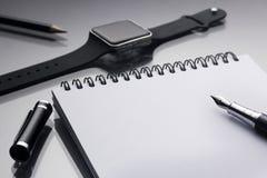 Белый блокнот на ем черная ручка около clos умных часов и карандаша Стоковые Фотографии RF