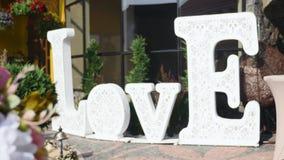 Белый большой знак при влюбленность слова стоя около партии или wedding банкета сток-видео