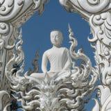 Белый Будда размышляя быть разделенным на голубом небе окруженном белыми орнаментами стоковая фотография