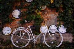 Белый велосипед стоит около кирпичной стены на фоне часов стоковое изображение