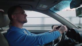 Белый водитель во взглядах автомобиля на правом заднем зеркале и улыбках взгляда Небо захода солнца r акции видеоматериалы