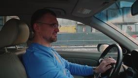 Белый водитель в автомобиле перед улыбками конструкции контролирует аудиосистему и кивает головой во времени  музыки Автомобиль д видеоматериал