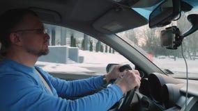 Белый водитель в голубых рубашке и стеклах управляет автомобилем вдоль снежного города на солнечном после полудня r сток-видео