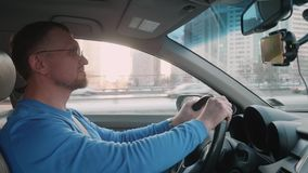 Белый водитель на руле автомобиля который настигнут автомобилями идя такой же путь Улыбки и thisnk человека над видеоматериал