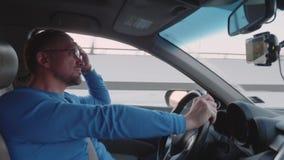 Белый водитель управляет автомобилем на высоком пути на высокой скорости с расслабленным взглядом сток-видео