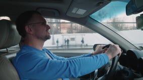 Белый водитель управляет автомобилем под мостом и улыбками Заход солнца в городе зимы акции видеоматериалы