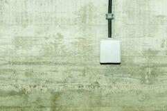 Белый выход электропитания при крышка и кабель с черной пропиткой крышки прикрепленные на бетонной стене grunge Стоковые Изображения RF