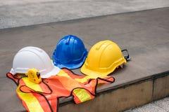 Белый, голубой, желтый трудный шлем безопасности на жилете с measuri Стоковые Изображения