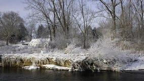 Белый Дом в солнечном свете в расстоянии со снегом покрыл траву и tress на речном береге во фронте стоковое изображение rf