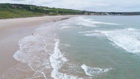 Белый залив парка, Северная Ирландия, антрим, дети играя на пляже, муха трутня сверх, отснятый видеоматериал 4k акции видеоматериалы