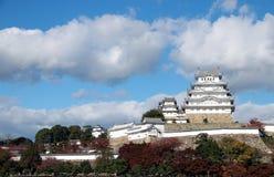 Белый замок Himeji на солнечном свете и красном цвете выходит осень на дерево с предпосылкой голубого неба Стоковые Изображения