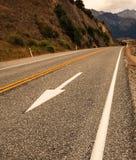 Белый знак уличного движения стрелки, желтые линии раздела и белая тропа выравниваются на дороге асфальта сельской стоковое изображение rf
