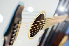 Белый или светлый - голубой деревянный конец акустической гитары вверх Освещает предпосылку Ядровое отверстие стоковые изображения rf