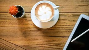 Белый кактус экрана и ручки черноты выставки таблетки и чашка кофе стоковое изображение