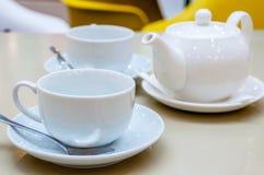 Белый керамический чай 2 mugs с сияющими ложками и поддонниками Стоковое Фото