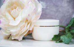 Белый косметический контейнер на белизне, украшенной с большим цветком Стоковое Изображение RF
