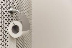 Белый крен мягкой туалетной бумаги аккуратно вися на современном держателе хрома на светлой стене ванной комнаты Стоковые Изображения