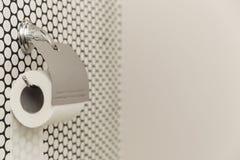 Белый крен мягкой туалетной бумаги аккуратно вися на современном держателе хрома на светлой стене ванной комнаты Стоковое Изображение RF