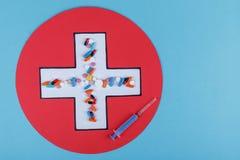 Белый крест в красном круге, внутри таблетки и шприц Сухой завтрак в ложке стоковые изображения