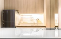 Белый лоснистый countertop и на предпосылке комнаты кухни нерезкости стоковые фото