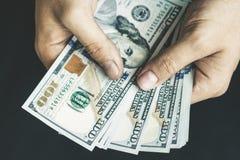 Белый молодой человек подсчитывает деньги, 100 новых долларовых банкнот на черном плане конца предпосылки Стоковая Фотография