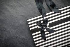 Белый пакет в черной нашивке с лентами ручек и черном открытом космосе смычка Стоковые Изображения