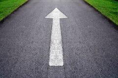 Белый передний знак стрелки на серой дороге асфальта Стоковое Изображение