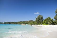 Белый песок коралла и azure индийский океан. Стоковая Фотография