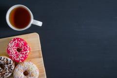Белый, пинк и коричневый застекленный donuts с чашкой чаю в левой стороне на черной деревянной предпосылке стоковое фото rf