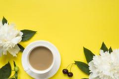 Белый пион цветет чашка кофе ягод вишни на желтой яркой предпосылке Стоковая Фотография