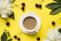 Белый пион цветет чашка кофе ягод вишни на желтой яркой предпосылке Стоковое фото RF