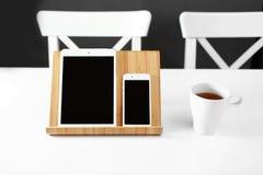 Белый планшет и смартфон на стойке на белом рабочем месте офиса таблицы кружка чая в рабочем месте стоковое фото rf
