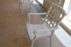 Белый пластичный стул стоит в комнате бассейна около окна, зоне отдыха Стоковые Изображения