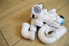 Белый пластичный трубопровод, трубы трубопровода, ровный и изогнутый, штуцеры, фланцы, резиновые набивки стоковое изображение rf
