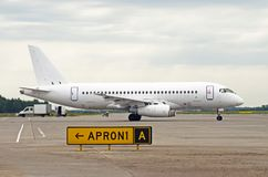 Белый самолет пассажира ездя на такси на авиапорте Стоковые Изображения
